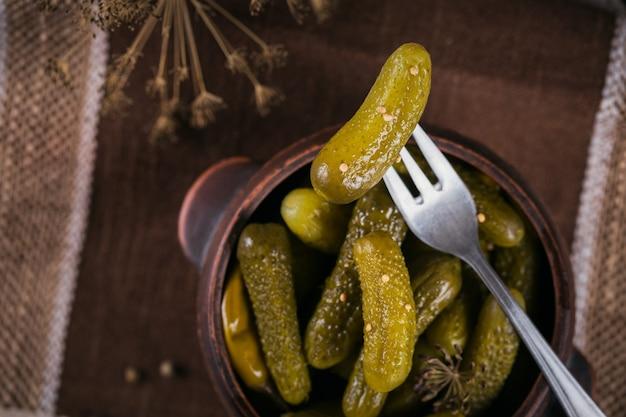 Augurken, ingelegde komkommer op een vork, kom met gemarineerde groenten op rustieke houten ondergrond. schoon eten, vegetarisch voedselconcept