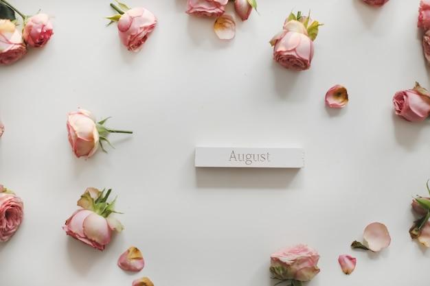 Augustus woorden op houten blok en rozen op witte achtergrond