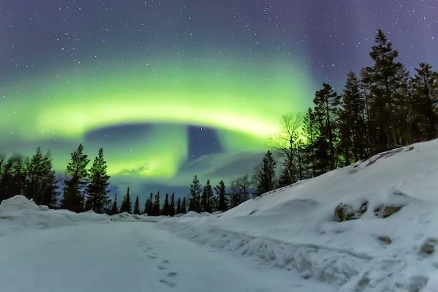 Aurora borealis aan de horizon over besneeuwde weg