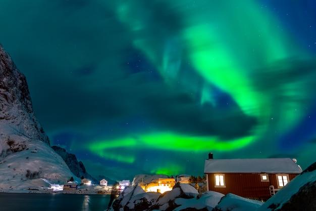 Aurora borealis boven de daken van huizen