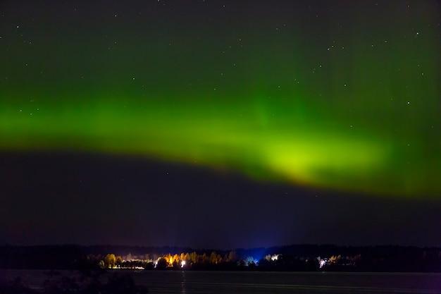 Aurora borealis boven de stad aan de kust. poollicht in de nachtelijke sterrenhemel boven het meer.