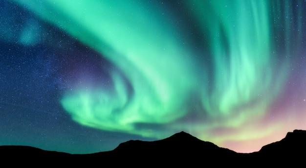 Aurora borealis en silhouet van bergen