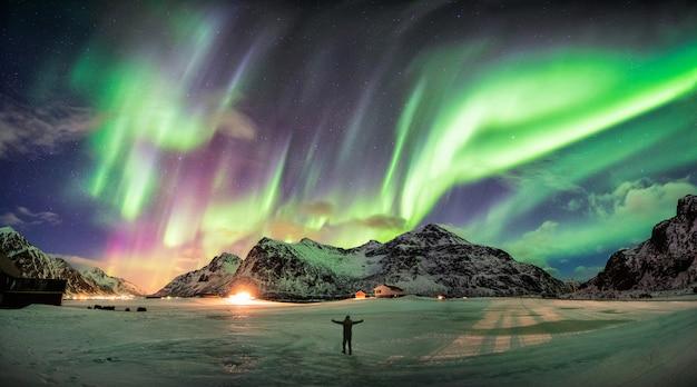 Aurora borealis (noorderlicht) over berg met één persoon