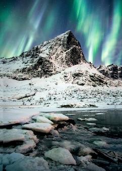 Aurora borealis noorderlichtexplosie over bergen in gletsjer op lofoten-eilanden