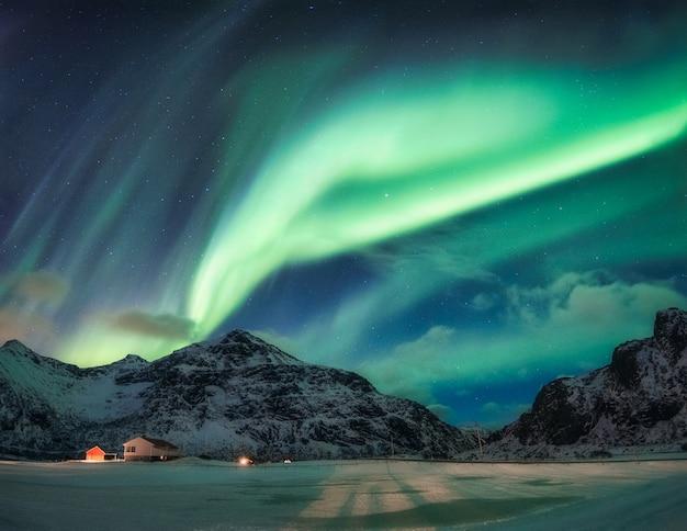 Aurora borealis of noorderlicht over besneeuwde berg op poolcirkel in flakstad op de lofoten-eilanden