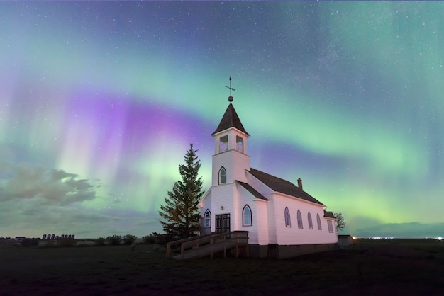 Aurora borealis over een historische kerk van het land op de prairies in saskatchewan, canada