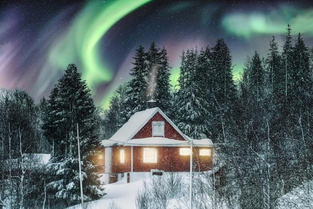 Aurora borealis over rood noords huis met sneeuw die op de winter in scandinavië wordt behandeld