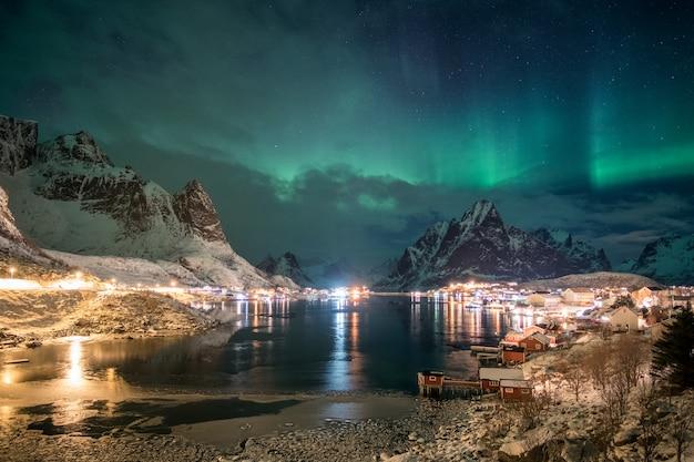 Aurora borealis over skandinavisch dorpslicht schijnt in de winter