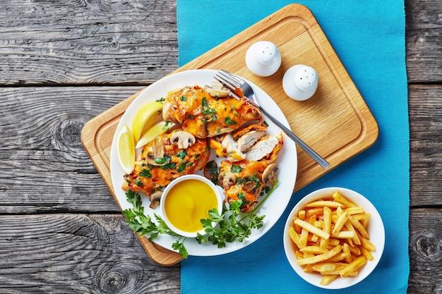 Aussie kipfilets gegarneerd met champignons, spek en gesmolten kaas gekookt in een honing-mosterdsaus geserveerd