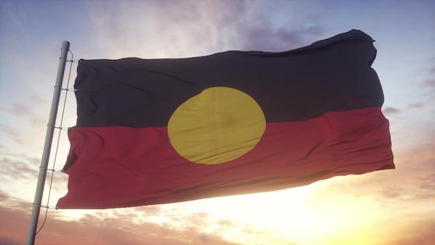 Australië aboriginal vlag zwaaien in de wind, lucht en zon achtergrond. 3d-rendering.