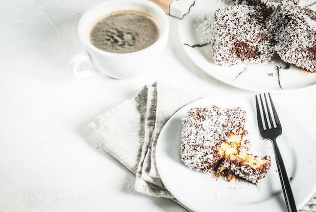 Australisch eten traditioneel dessert lamington - stukjes koekje in pure chocolade besprenkeld met kokospoeder chips op een marmeren bord witte tafel met koffiemok