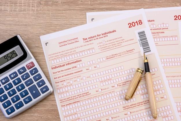 Australische belastingaangifte en pen op houten tafel