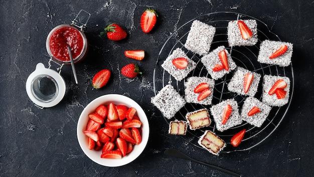 Australische dessertlamingtons met aardbeienjamvulling, omhuld met chocolade en geraspte kokos, geserveerd op een rond rooster