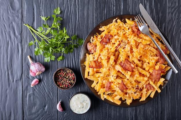Australische frietjes met gesmolten mix van geraspte kaas en spek geserveerd op een bord op een zwarte houten tafel met ranch dressing in een juskom