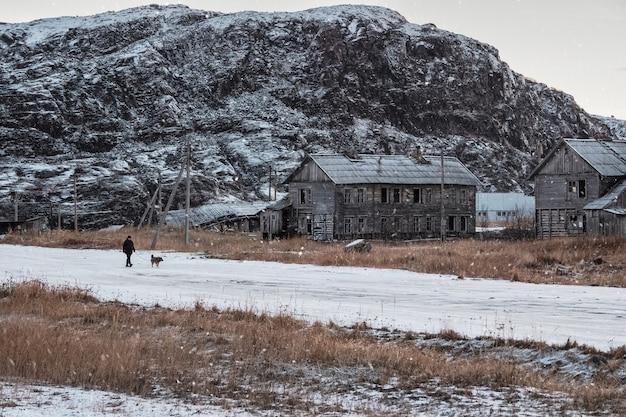 Authentiek russisch noordelijk dorp, oude vervallen houten huizen, ruige arctische natuur. een man loopt met een hond.