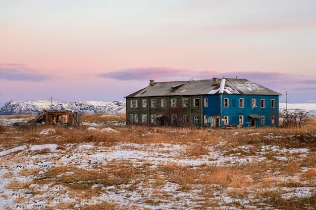 Authentiek russisch noordelijk dorp, oude vervallen houten huizen, ruige arctische natuur. teriberka.