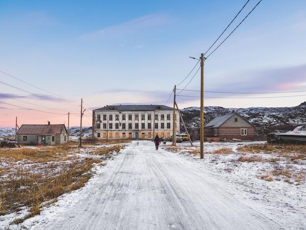 Authentiek russisch noordelijk dorp, oude vervallen houten huizen, ruige arctische natuur