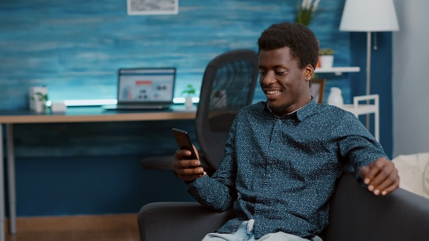 Authentieke afro-amerikaanse man op virtuele communicatie video-oproep met behulp van zijn telefoon om te praten met rela...