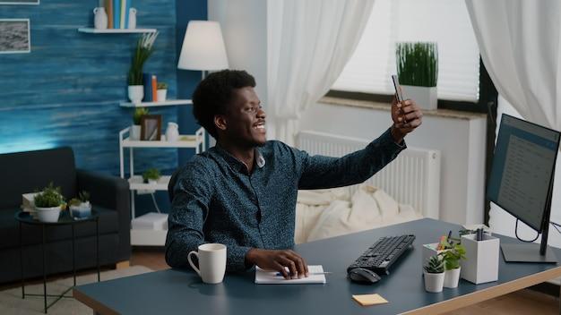 Authentieke afro-amerikaanse zwarte man die selfie neemt in een gezellige woonkamer terwijl hij op afstand thuis werkt. persoon die foto maakt voor sociale media met modernere mobiele smartphone
