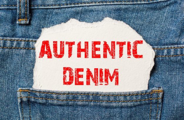 Authentieke denim op wit papier in de zak van een blauwe spijkerbroek