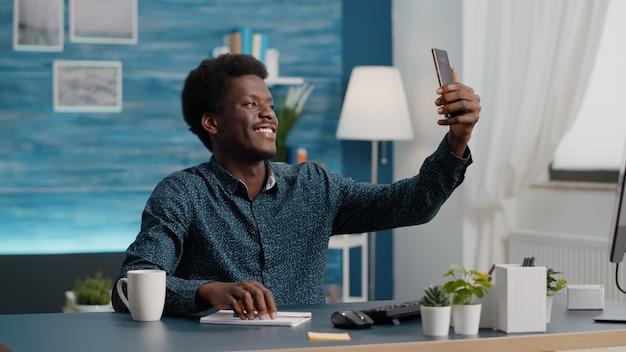 Authentieke gelukkige afro-amerikaanse man die lacht en een selfie neemt in de woonkamer om deze op sociale media te delen. mobiele foto, online vrijetijdsbesteding op internet voor zwarte mannen