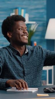 Authentieke gelukkige jonge man die lacht en een selfie neemt in de woonkamer om deze te delen op sociale media