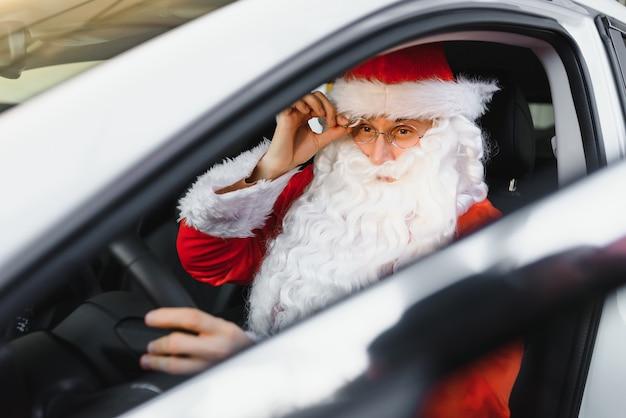 Authentieke kerstman die buiten in zijn moderne auto rijdt