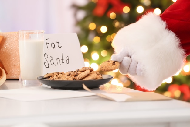 Authentieke kerstman die koekje van bord neemt tegen wazige kerstverlichting