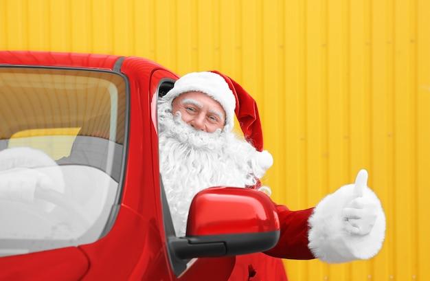 Authentieke kerstman in auto met duim omhoog gebaar