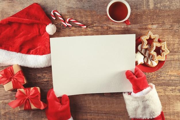 Authentieke kerstman met brief aan houten tafel