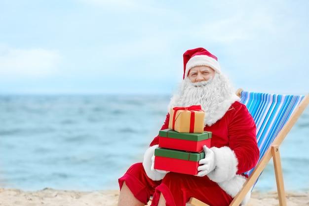 Authentieke kerstman met geschenkdozen in ligstoel op strand