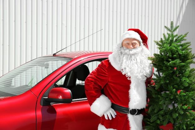 Authentieke kerstman met kerstboom die buiten in de buurt van rode auto staat