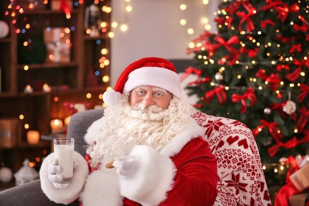 Authentieke kerstman met koekje en glas melk zittend in fauteuil in kamer ingericht voor kerstmis