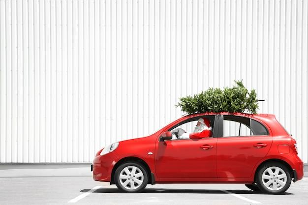 Authentieke kerstman rijdende auto met dennenboom op zijn top