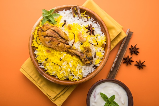 Authentieke kip biryani geserveerd in een kom of bord op kleurrijke of houten achtergrond. het is een heerlijk recept van basmati rijst gemengd met pittig gemarineerde kip geserveerd met salade. selectieve focus