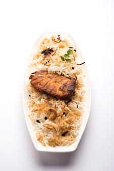 Authentieke vis biryani geserveerd in een witte plaat op een witte achtergrond, selectieve focus