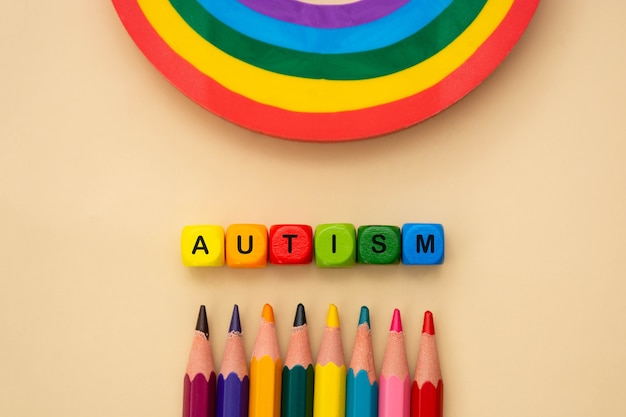 Autisme woord houten kleurrijke kubussen en regenboog. geestelijke gezondheid, sociale ondersteuning. speciaal onderwijsconcept.