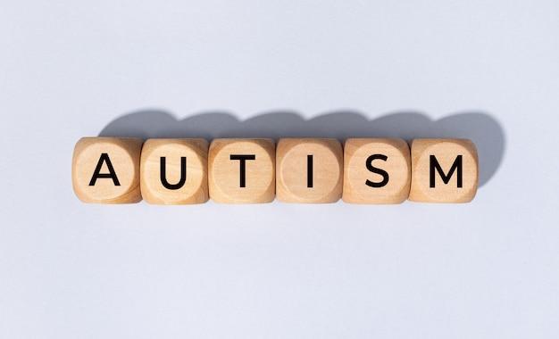 Autisme woord op houten blok geïsoleerd op een grijze achtergrond