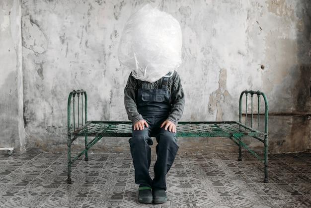 Autist wikkelt zijn hoofd in verpakkingsfolie, grunge kamerinterieur.