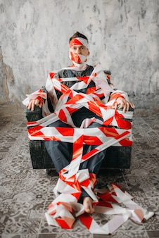 Autistische zittend op een stoel in het midden van de kamer