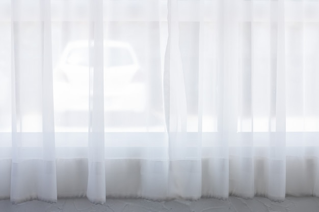 Auto achter raam heeft prachtige witte gordijnen voor de achtergrond. in het ochtendlicht.