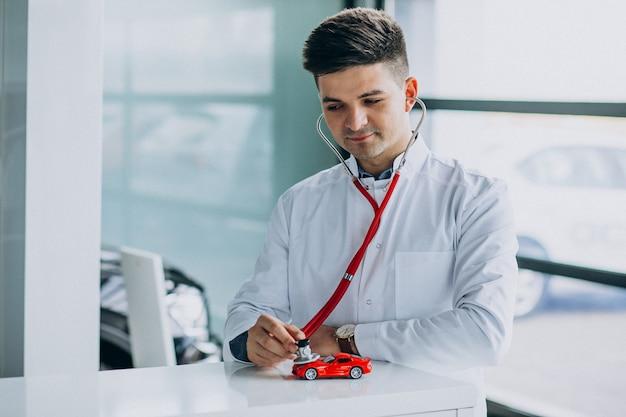 Auto arts met een stethoscoop in een autotoonzaal