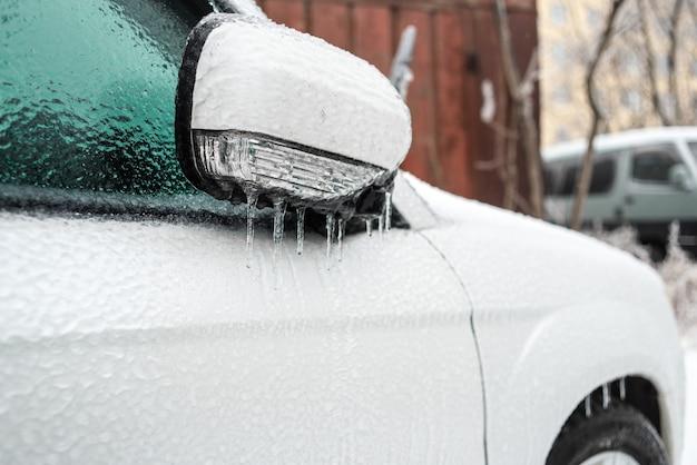 Auto bedekt met ijs en ijspegels na ijzel slecht ijzig weer ijstorm cycloon winter besneeuwde scènes