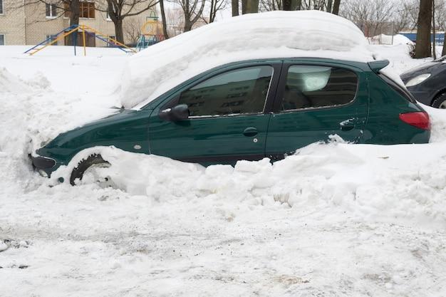 Auto bedekt met zware sneeuwjacht na zware wintersneeuwval