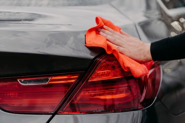 Auto concept schoonmaken. mans hand afvegen van de motorkap met microvezeldoek.