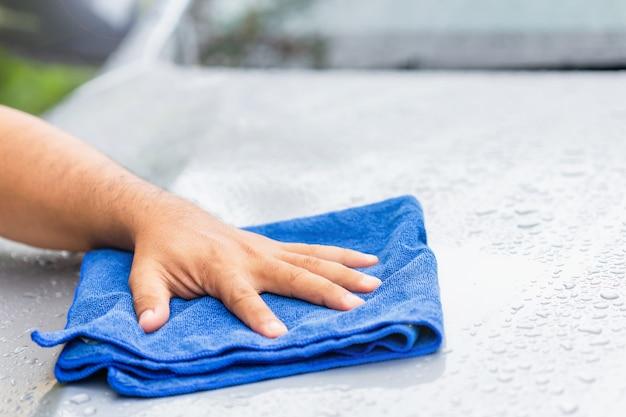 Auto concept schoonmaken of wassen: hand met blauwe doek om het natte lichaam van de moderne auto te reinigen. buiten fotograferen op een regenachtige dag.