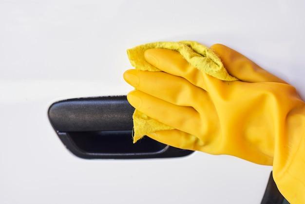 Auto desinfectieservice. vrouw die het handvat van de autodeur desinfecteert