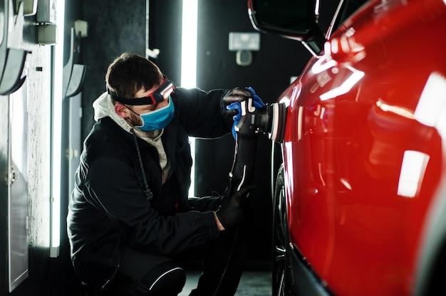 Auto detaillering concept. man in gezichtsmasker met orbitale polijstmachine in reparatiewerkplaats oranje suv auto polijsten.