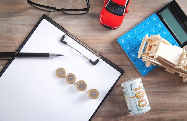 Auto, dollarbiljetten, rekenmachine op het bureau.