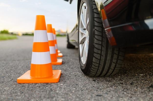 Auto en oranje verkeerskegels, les in rijschoolconcept, niemand. lesgeven om voertuigthema te besturen. rijbewijs opleiding